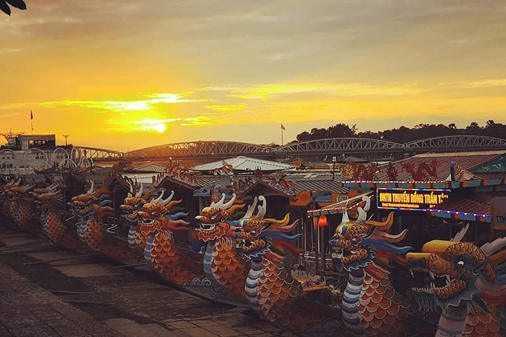 Dragon boats lined up on the Perfume River at sunset