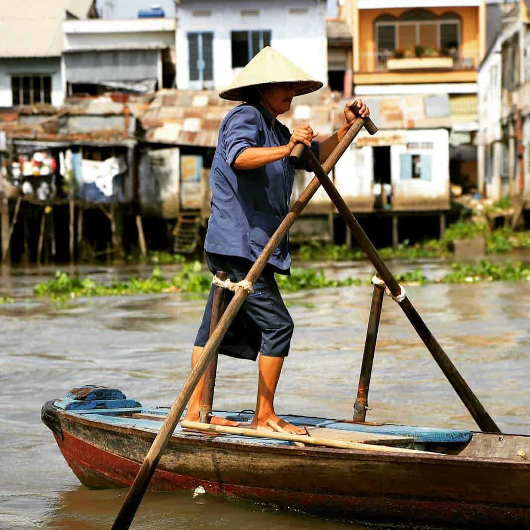 A local woman sailing boat on the river - history of Cai Be Floating market