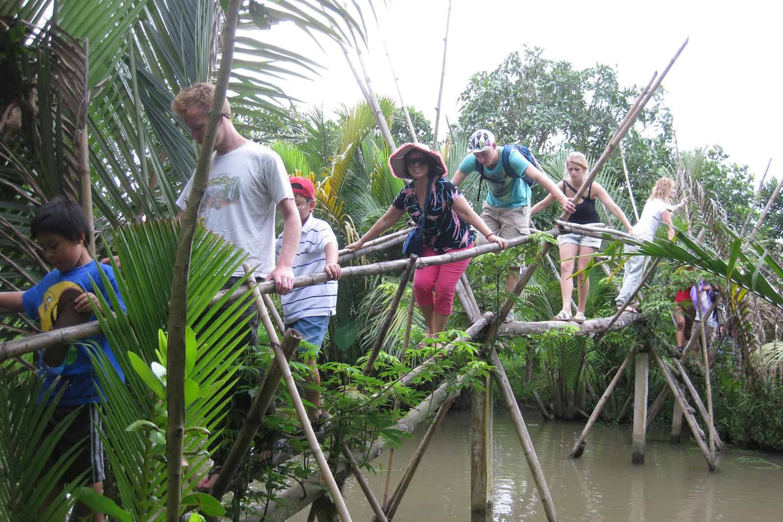 Tourists experience the game of crossing monkey bridge in mekong delta